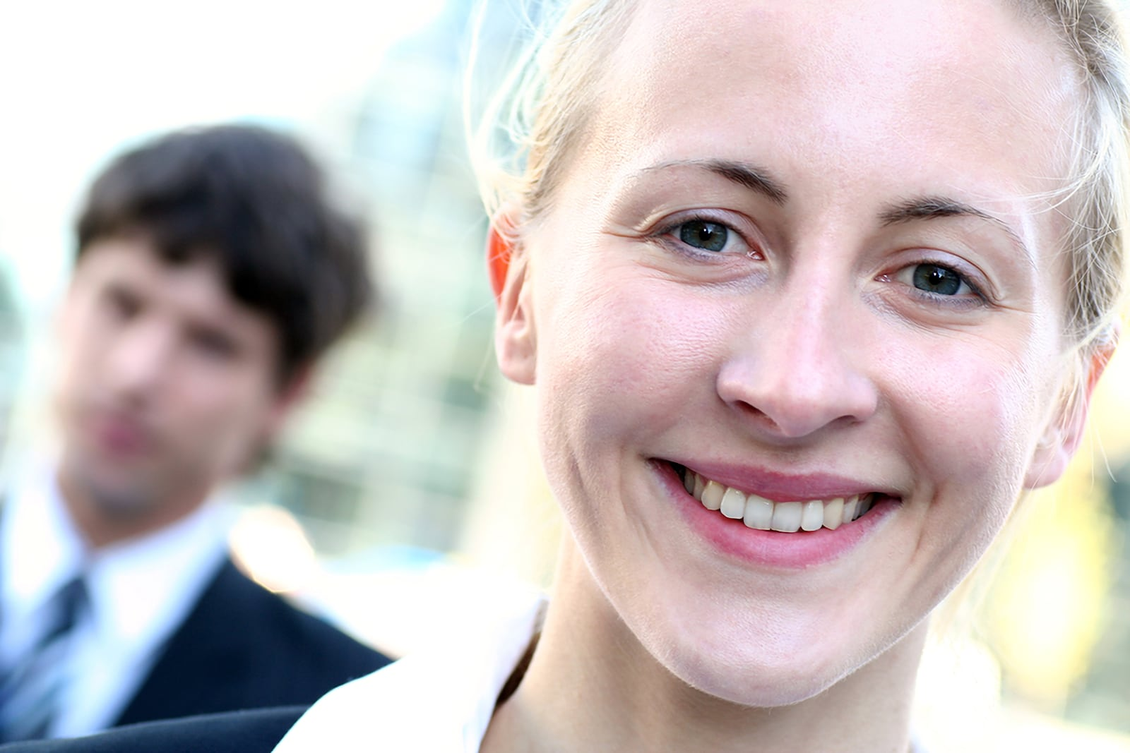 Photo of male and female business people outdoors. Younger blond haired female head shot is in focus, closer to the camera, and smiling. Younger white male is further away from the camera and out of focus
