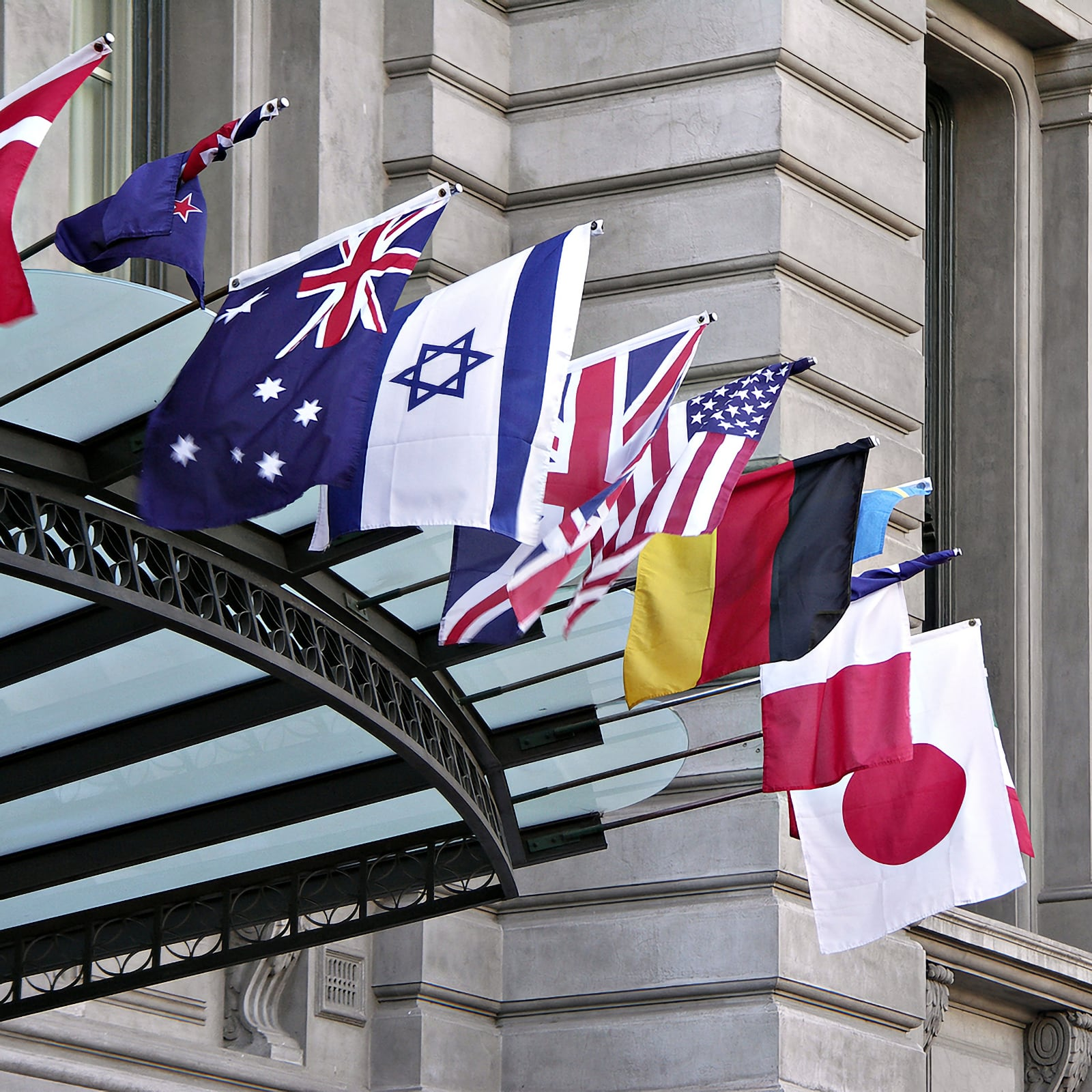 Photo of various world flags flying above entrance to a classic stone building