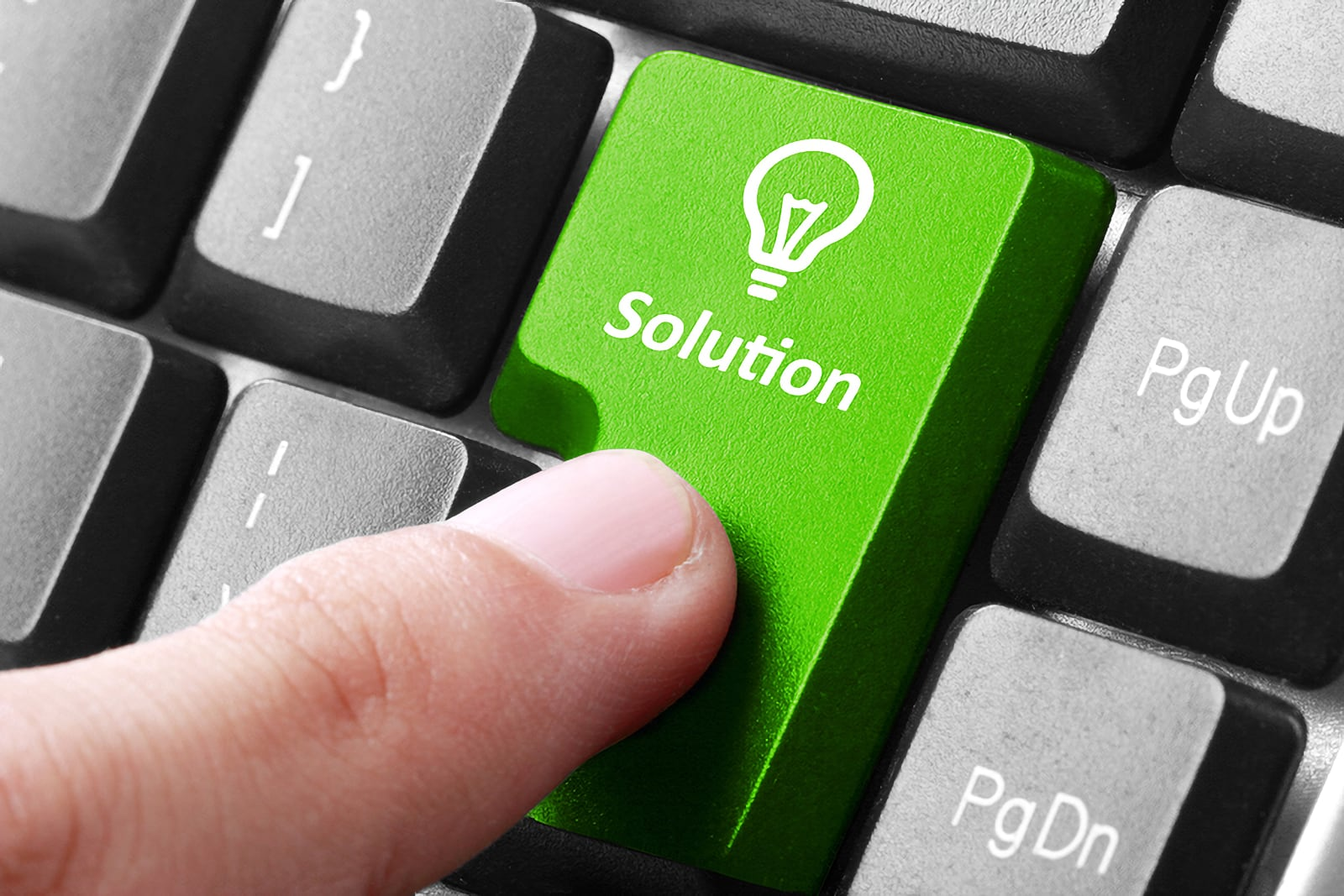 Photo concept of dark-coloured computer keyboard with larger green button showing the word Solution and a lightbulb icon