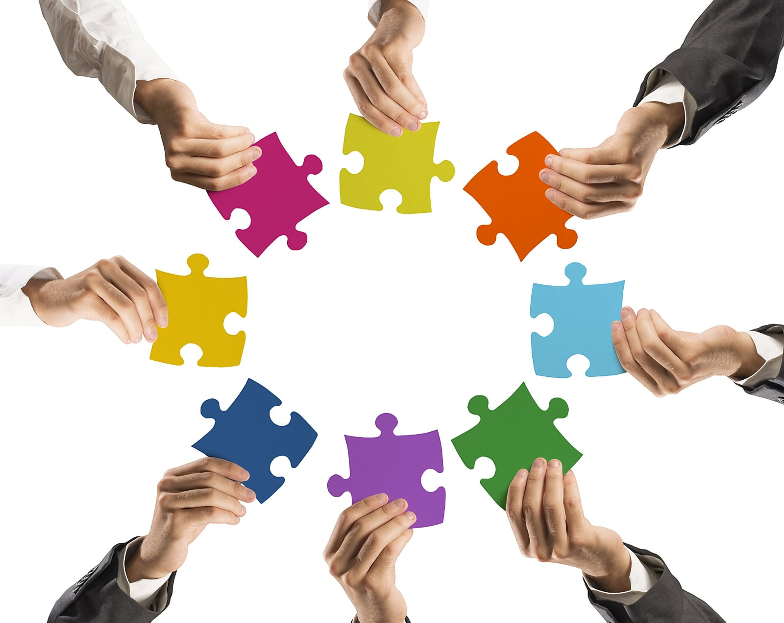Concept image showing seven indvidual hands each holding a piece of a coloured jigsaw puzzle. Each and presents their jigsaw puzzle piece to the centre of the group to all form a circle of contribution