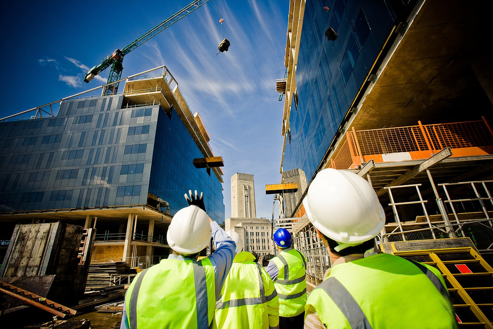 Photo of UK building site with high rise cranes moving goods, and workers with hard hat protection evaluating progress