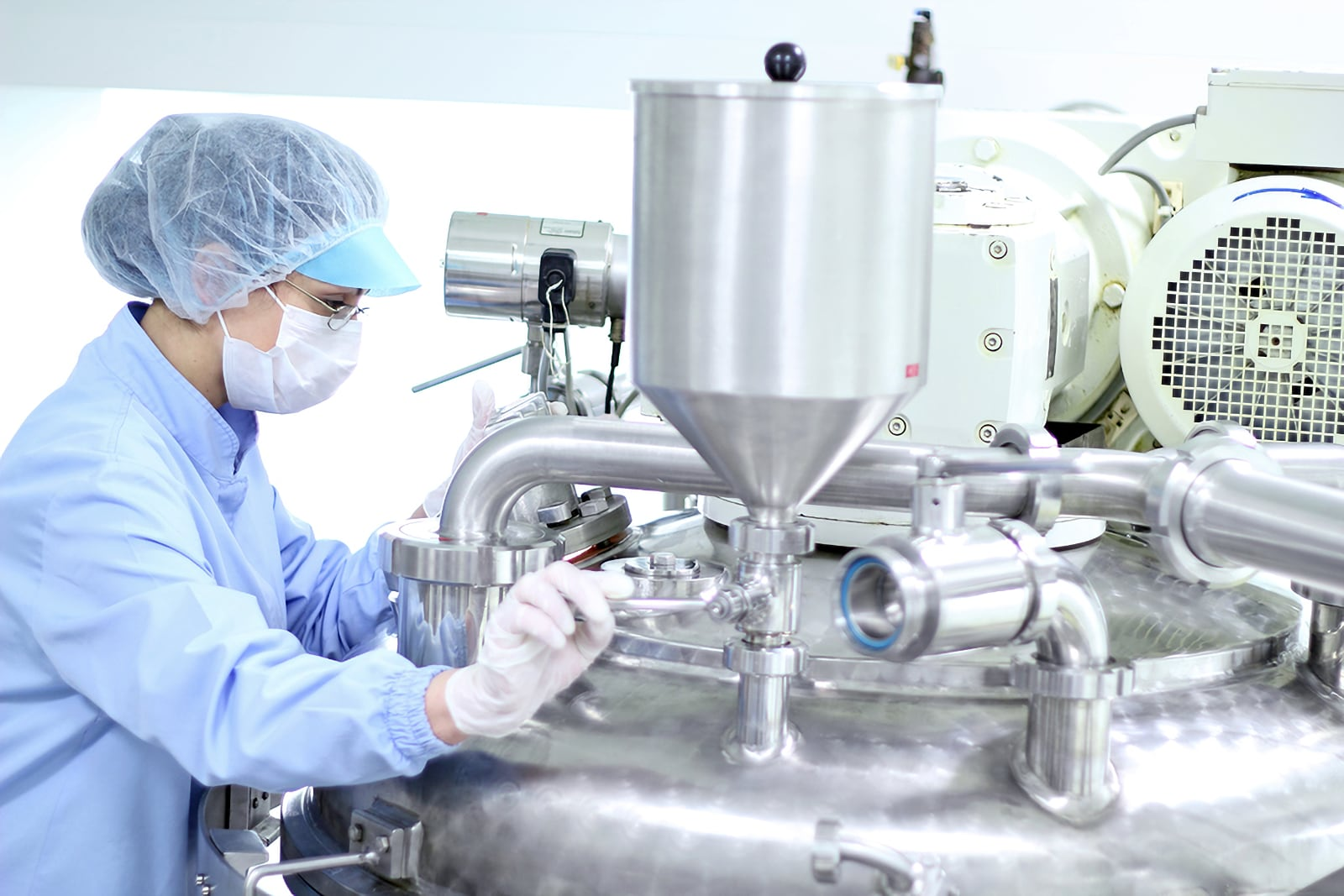Photo of pharmaceutical worker with facemask, hair net, gown, and gloves, processing chemicals working at an industrial machine