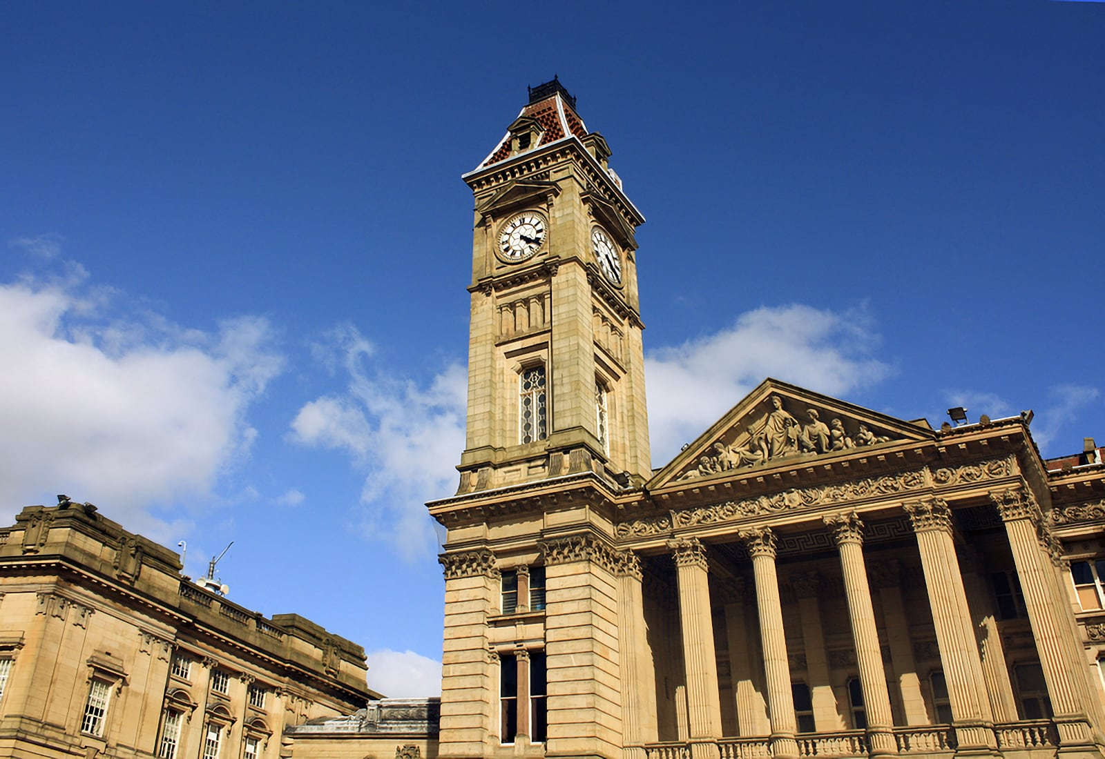 Photo looking up at Birmingham city council clock tower and building against a mostly blue sky background