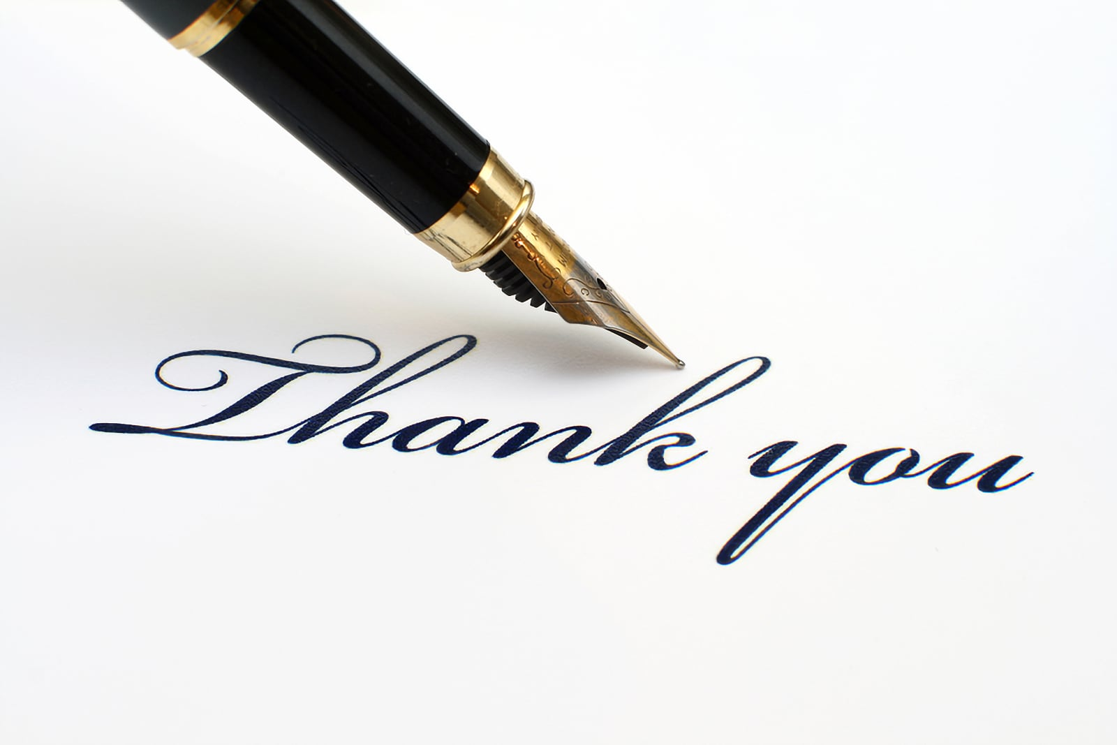 Close-up photo of beautiful fountain pen pointing at the words Thank you, writen in handwriting script on paper