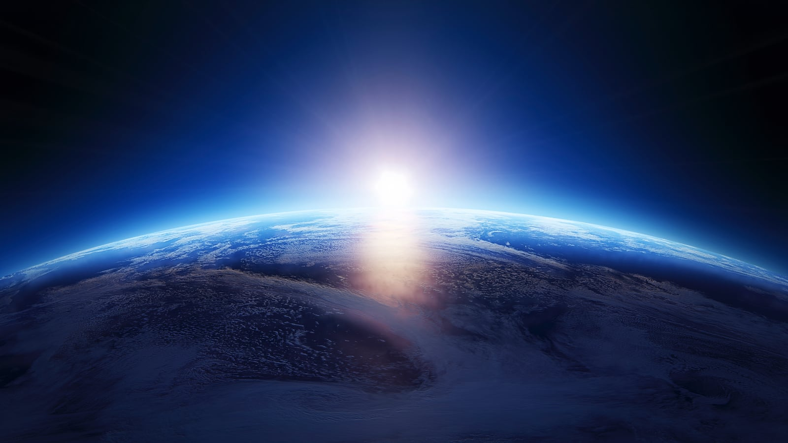 Photo of part Earth curvature from space, with the sun just coming into view behind the Earth