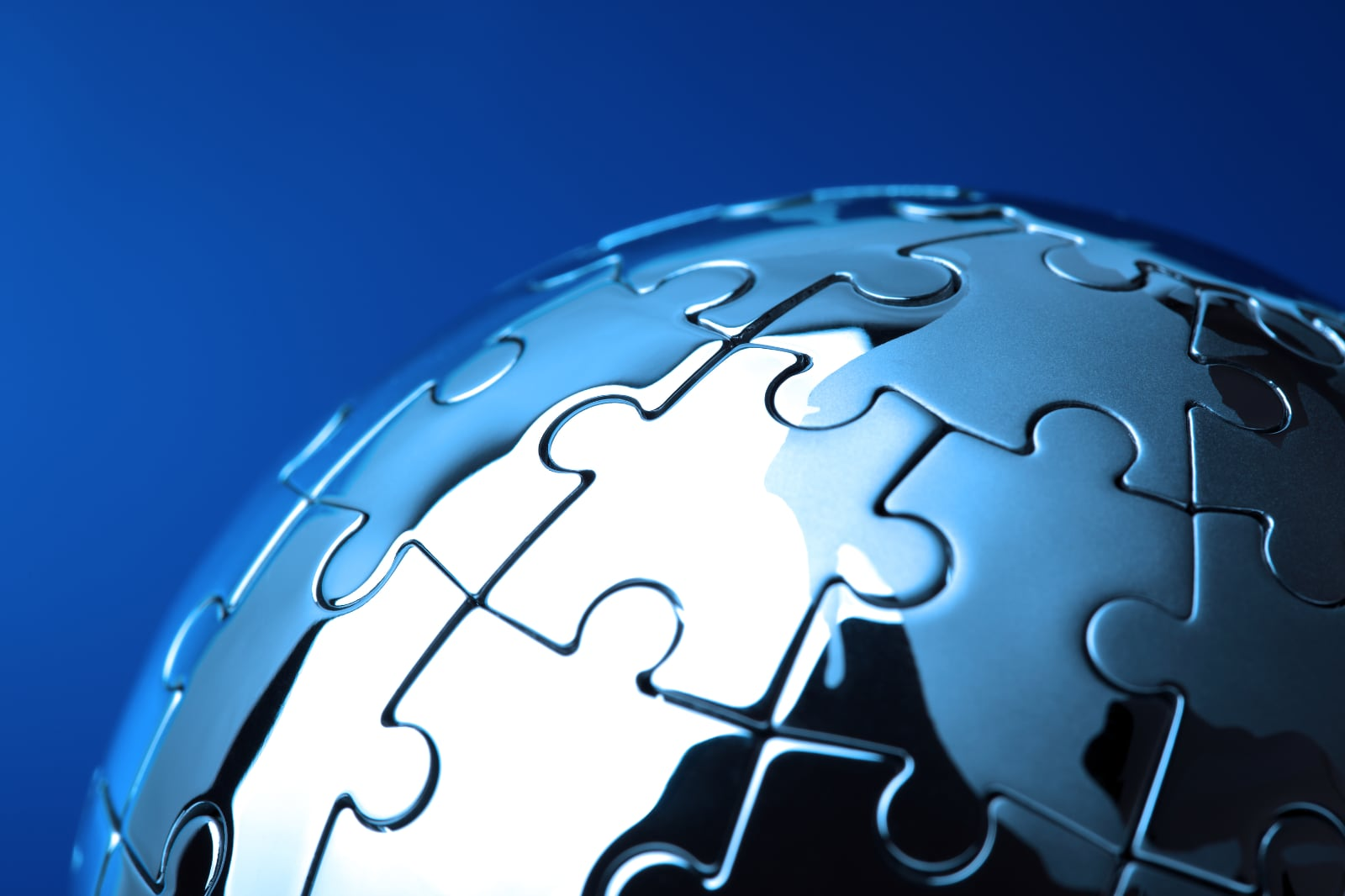 A completed three dimentional silver metallic jigsaw puzzle in the shape of a sphere or globe, with a blue background